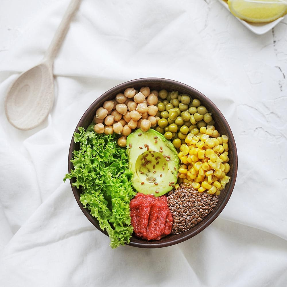 Salad bowl with chickpeas, peas, avocado, corn grains, seeds, tomato purée and lettuce from La Española Olive Oil Instagram